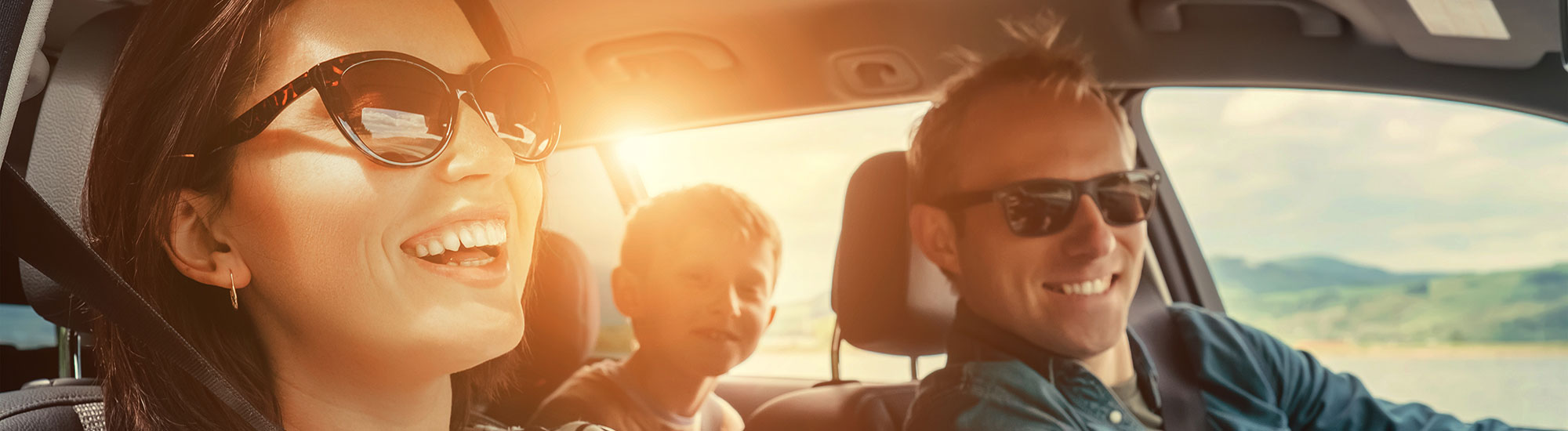 smiling family riding in car